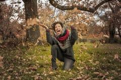愉快的妇女画象获得与叶子的乐趣在秋天 免版税库存图片