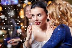 愉快的妇女说闲话在雪的夜总会 库存照片