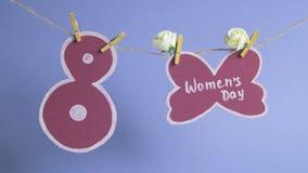 愉快的妇女` s天 妇女在用花装饰的纸的` s天,垂悬在绳索在纸第8附近 背景看板卡祝贺邀请 股票录像