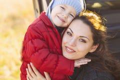 愉快的妈咪和走在海滩的女婴在秋天 免版税库存照片