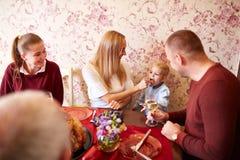 愉快的妈妈和儿子圣诞节或感恩晚餐的在欢乐背景 家庭接合概念 免版税图库摄影