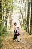 愉快的妈妈和女儿在举行手和微笑的公园跌倒 库存图片