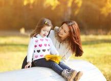 愉快的妈妈和女儿获得乐趣户外在秋天 免版税库存图片