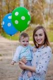 愉快的妈妈和婴孩举行气球、妈妈和孩子获得乐趣在夏天自然,手,自由概念喜悦 库存图片