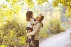 愉快的妈妈和孩子在秋天 免版税图库摄影