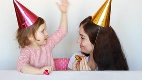 愉快的妈妈和孩子生日聚会的,打在比赛 照顾她的女儿微笑和laughes在白色背景 股票录像