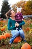 愉快的妈妈和婴孩南瓜补丁的 免版税库存图片