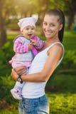 愉快的妈妈和婴孩在夏天停放 免版税图库摄影