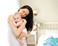 愉快的妈妈在卧室拥抱婴孩,家 免版税库存图片