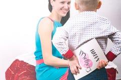 愉快的妈妈天:小男孩掩藏在他后的贺卡 免版税库存图片