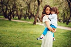 愉快的妈妈拥抱和亲吻小孩哄骗儿子室外在春天或夏天 免版税库存照片
