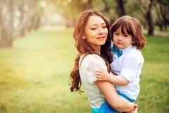 愉快的妈妈拥抱和亲吻小孩哄骗儿子室外在春天或夏天 图库摄影