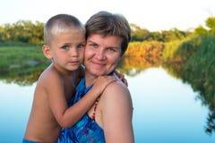 愉快的妈妈拥抱他的年轻儿子 免版税库存图片