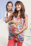 愉快的妊妇和女儿 免版税库存图片