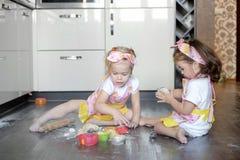 愉快的姐妹儿童女孩在厨房里烘烤曲奇饼,揉面团,使用用面粉和笑 库存照片