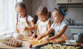 愉快的姐妹儿童女孩烘烤曲奇饼,揉面团,戏剧机智 库存图片