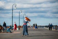 愉快的姜女孩步行击倒街道 免版税库存图片