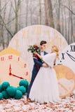 愉快的婚礼夫妇软软地拥抱在秋天森林创造性的装饰的大葡萄酒时钟 图库摄影
