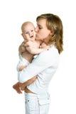 愉快的婴孩她亲吻的母亲 免版税库存图片
