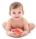 愉快的婴孩用在她的现有量的一个大苹果。 免版税库存照片