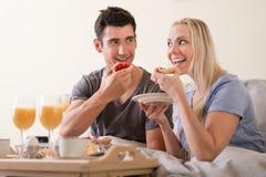 愉快的嬉戏的夫妇在床上的享用早餐 免版税库存照片