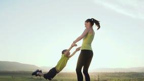 愉快的子项 母亲使用与自然的孩子在日落在训练从赛跑以后 年轻母亲是 股票视频