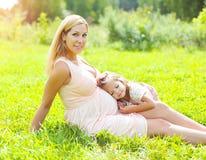 愉快的孕妇、说谎在草的微笑的母亲和孩子在夏天 免版税图库摄影