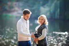 愉快的孕妇和她的丈夫在步行期间与一个人在湖附近 库存图片