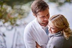 愉快的孕妇和她的丈夫在步行期间与一个人在湖附近 库存照片