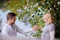 愉快的孕妇和她的丈夫在步行期间与一个人在湖附近 免版税库存图片