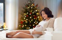 愉快的孕妇在家圣诞节的 免版税库存照片