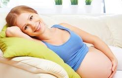 愉快的孕妇在家基于沙发 图库摄影