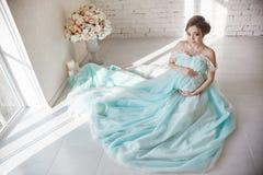 愉快的孕妇在长的晚礼服感人的腹部手上 等待孩子的诞生,一名妇女在她的第八个月 库存照片