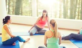 愉快的孕妇坐在健身房的席子 免版税图库摄影
