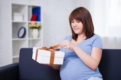 愉快的孕妇开头礼物盒在客厅 免版税库存图片