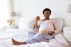 愉快的孕妇用新月形面包小圆面包在家 库存照片