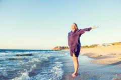 愉快的孕妇胳膊上升了由天空决定,享用在与自然的平衡和庆祝在海滩的自由 正面e 免版税库存图片