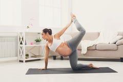 愉快的孕妇训练瑜伽在家 免版税图库摄影