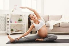 愉快的孕妇训练瑜伽在家 免版税库存照片