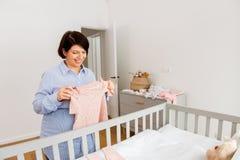 愉快的孕妇设置婴孩衣裳在家 库存照片