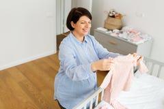 愉快的孕妇设置婴孩衣裳在家 免版税库存图片