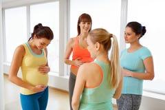 愉快的孕妇谈话在健身房 免版税库存图片