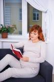 愉快的孕妇阅读书在家 图库摄影