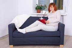 愉快的孕妇饮用的茶和阅读书在家 图库摄影