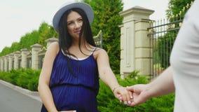 愉快的孕妇 她采取他的有他的丈夫 微笑,一起走在公园 股票视频