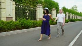 愉快的孕妇 她采取他的有他的丈夫 微笑,一起走在公园 股票录像