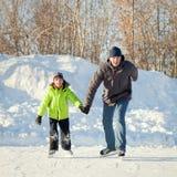 愉快的学会乐趣父亲和的儿子滑冰 免版税库存照片