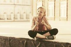 愉快的学校女孩坐在城市街道的边路 免版税库存图片