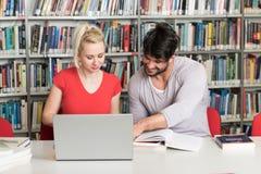 愉快的学生与膝上型计算机一起使用在图书馆里 库存图片