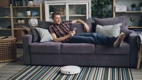 愉快的学生使用看屏幕和微笑的放松在舒适的长沙发的智能手机,当机器人真空时 影视素材